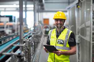 Portrait of smiling factory worker using a digital tablet