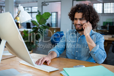Graphic designer using computer while talking on mobile phone