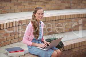 Portrait of schoolgirl using laptop in campus