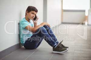 Schoolboy talking on mobile phone in corridor