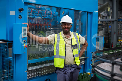 Smiling factory worker standing near machine control cabinet