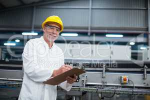Smiling factory engineer maintaining record on clipboard in factory