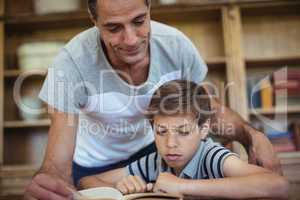 Father and son reading a book in study room