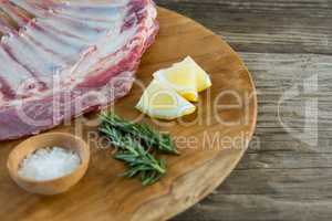 Beef ribs rack, rosemary herb, salt and lemon on wooden tray against wooden background
