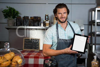 Male staff holding a digital tablet in coffee shop
