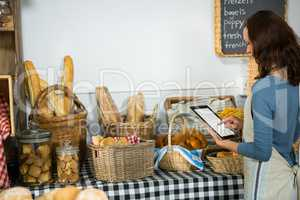 Attentive staff using digital tablet at bakery counter