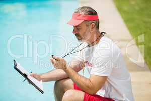 Swim coach looking at stopwatch near poolside