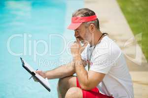 Swim coach looking at clipboard near poolside