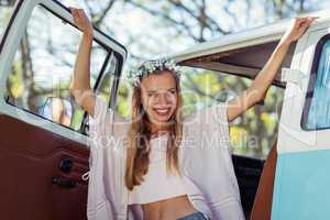 Woman with flower wreath standing in campervan