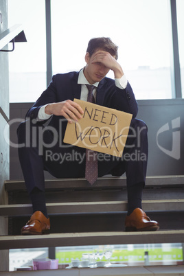 Depressed businessman sitting on stairs holding cardboard sheet with text need work