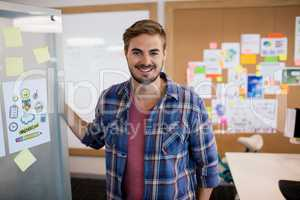 Smiling man standing near the wall with sticky notes