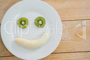 Banana and slice of kiwi in plate