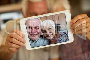 Senior couple taking selfie from digital tablet in kitchen