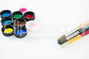 Colorful lids and paintbrushes on white background