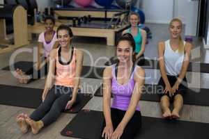 Group of smiling women performing stretching exercise