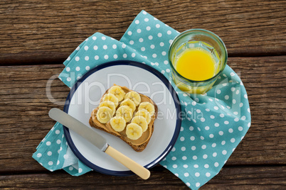 Sliced bananas spred on brown bread in plate with glass of juice