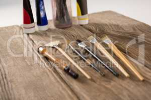Paintbrushes and watercolor tubes arranged on wooden surface