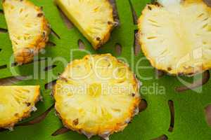 Close-up of slices and halved pineapple in tray