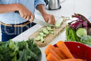 Mid-section of woman cutting vegetables on chopping board