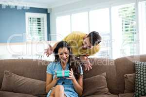 Young man giving a surprise gift to woman in the living room