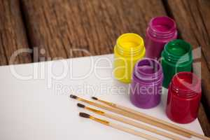 Paint brushes, watercolor paints and white paper