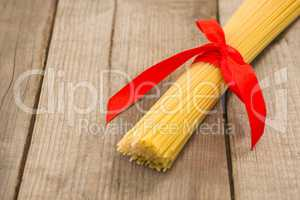 Bundle of raw spaghetti tied with red ribbon