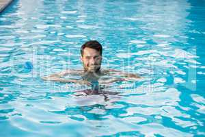 Young man swimming with inflatable tube