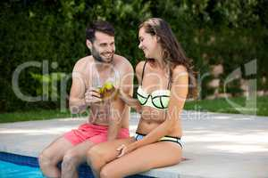 Young couple toasting glasses of iced tea at poolside
