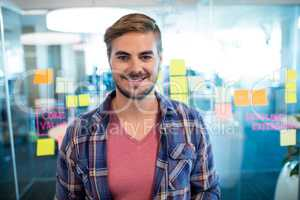 Smiling man standing against sticky notes on the glass wall in office