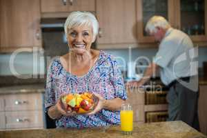 Senior woman holding bowl of fruit while man working in kitchen