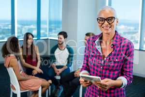 Woman using digital tablet while creative business team in background