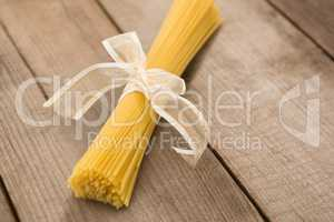 Bundle of raw spaghetti tied with white ribbon