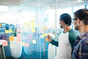 Creative business team looking at sticky notes and discussing