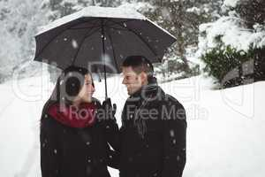 Smiling couple under umbrella standing in forest