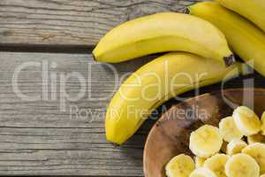 Banana and slices of banana in plate on wooden table