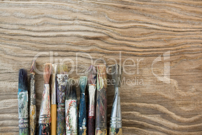 Various dirty paintbrush arranged in a row