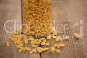 Conchiglie pasta spilled out of glass jar