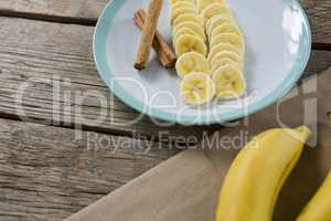 Banana and slices of banana with cinnamon stick in plate on wooden table
