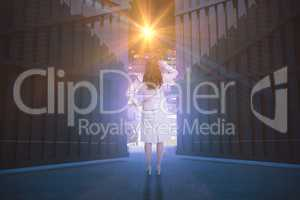 Composite image of businesswoman standing back to camera with hand on head 3d