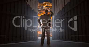 Composite image of businessman standing back to the camera with hand on head 3d