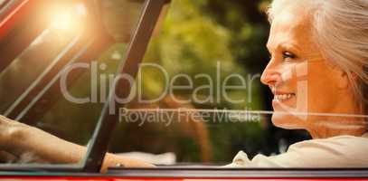 Smiling mature woman driving red convertible