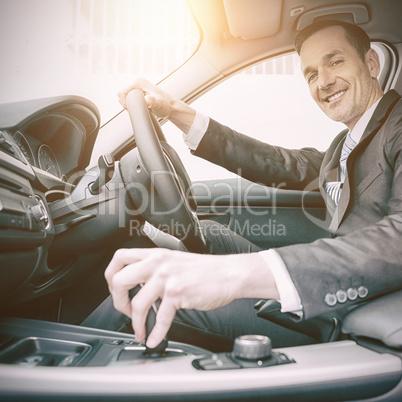 Man driving a car and smiling at camera