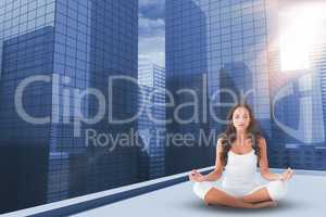 Composite image of pretty brunette doing yoga