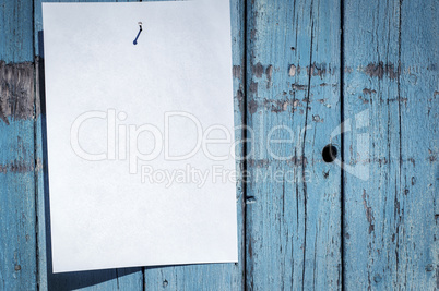 blank white piece of paper hanging on a nail
