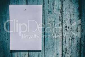 white sheet of paper hangs on a blue wooden wall