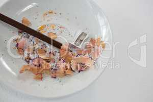 Colored shavings with brown color pencil and sharpener in saucer