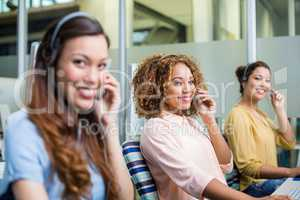 Portrait of female customer service executives talking on headset at desk
