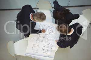 High angle view of businesspeople discussing over blueprint