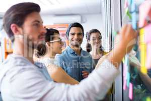Executives writing on sticky notes on glass wall
