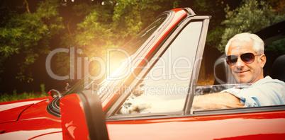 Handsome man enjoying his red convertible
